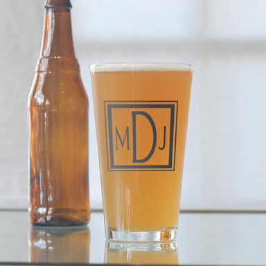 Custom square monogram 16 oz. pint glass filled with beer