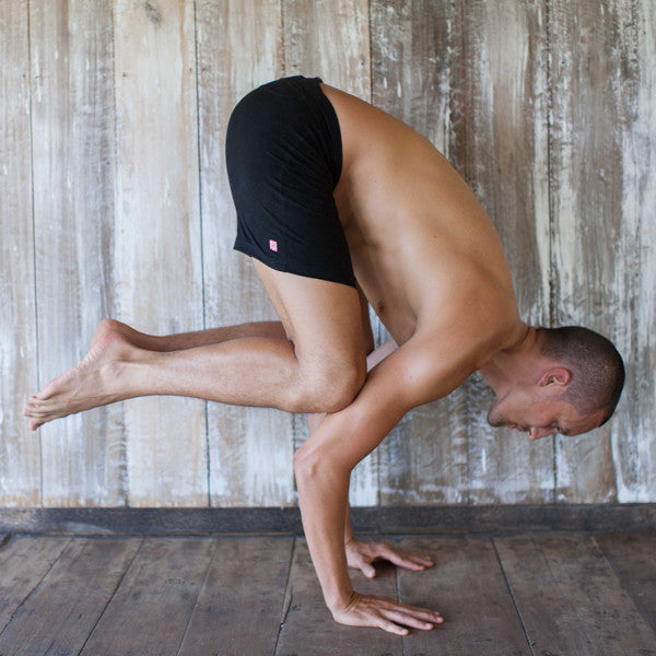 man in crow pose in wear yoga shorts