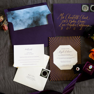 A dark, luxurious letterpress wedding invitation. The announcement card has a gold foil sunburst and an octagon cutaway revealing white cotton paper with plum letterpress beneath. The RSVP card is blind debossed with the sunburst pattern and also features plum letterpress; the main envelope is plum with a smoky envelope liner; the stamps feature the lunar eclipse, enhancing the moody, witchy vibe.
