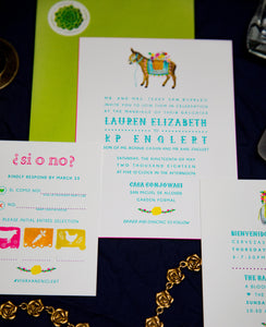 Mexican letterpress wedding invitation with watercolor illustrations of papel picado, burro with flowers, and a tequila bottle with a bouquet, arranged in a flat lay. Features bright colors and playful text and a lime green envelope