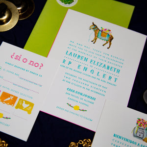 Mexican letterpress wedding invitation with watercolor illustrations of papel picado, burro with flowers, and a tequila bottle with a bouquet. Bright colors and playful text. Lime green envelope