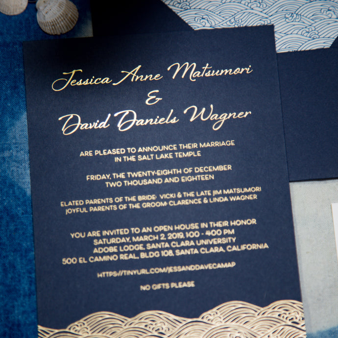 A navy blue invitation with gold foil printing depicting text and ocean waves. The waves are in a stylized japanese wave pattern called
