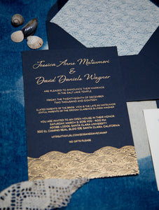 "A navy blue invitation with gold foil printing depicting text and ocean waves. Envelope liner with the same pattern in blue on ivory. The waves are in a stylized japanese wave pattern called ""seigaiha"""