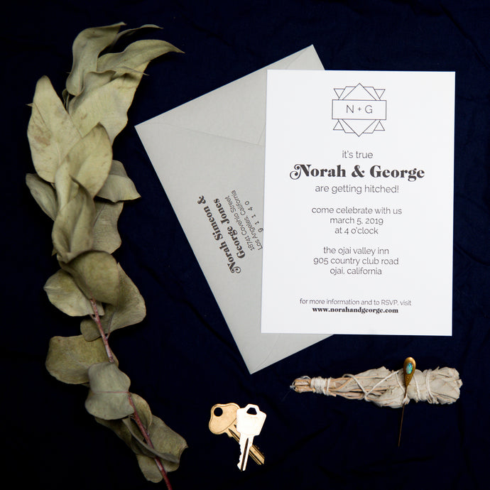 Hip modern letterpress wedding invitation with swooping 1970s font for the names, a custom monogram crest, and fun sans serif typeface. Arranged in a flat lay with a gray envelope, keys, leaves, and herbs