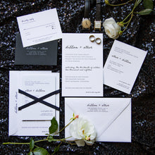 Load image into Gallery viewer, Modern letterpress wedding invitation for a chic, minimalist black tie wedding. Features hand lettering and a block serif typeface, a black RSVP envelope and a black silk ribbon. Arranged in a flat lay.