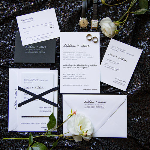 Modern letterpress wedding invitation for a chic, minimalist black tie wedding. Features hand lettering and a block serif typeface, a black RSVP envelope and a black silk ribbon. Arranged in a flat lay.