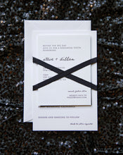 Load image into Gallery viewer, Modrn letterpress wedding invitation for a chic, urban black tie wedding. Features hand lettering and a block serif typeface, and tied a black silk ribbon in an X pattern.