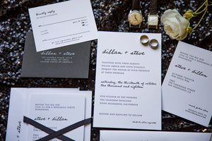 Modern letterpress wedding invitation for a hip, urban black tie wedding. Features a modern handwritten font and a small-caps serif typeface, a black RSVP envelope and a black silk ribbon. Arranged in a flat lay.