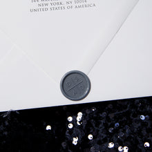 Load image into Gallery viewer, Detail shot of the custom wax seal for this wedding invitation, which features the monogram of the couple in a classic font. The wax seal is gray and the envelope is white, with return address letterpress printed on the flap.