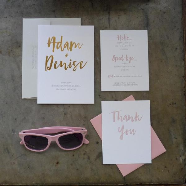 Modern letterpress wedding invitation with gold foil brush lettering, blush and grey letterpress, and pale pink envelope flat lay