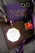 Load image into Gallery viewer, A dark purple wedding invitation with a gold foil sunburst pattern is arranged with a moonstone ring and purple ribbon. In the center of the invitation is an octagon cutaway revealing plum colored letterpress on white paper. The envelope is also violet, with gold calligraphy and lunar eclipse stamps.