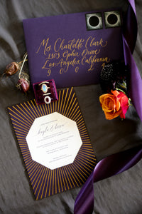 A dark purple wedding invitation with a gold foil sunburst pattern is arranged with a moonstone ring and purple ribbon. In the center of the invitation is an octagon cutaway revealing plum colored letterpress on white paper. The envelope is also violet, with gold calligraphy and lunar eclipse stamps.