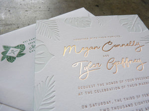 Letterpress wedding invitation with Palm and Monstera leaves and gold foil detail shot with custom monogram