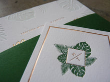 Load image into Gallery viewer, Letterpress wedding invitation with Palm and Monstera leaves and gold foil detail shot with custom monogram belly band enclosure
