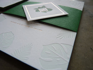 Letterpress wedding invitation with Palm and Monstera leaves and gold foil detail shot with custom monogram belly band enclosure