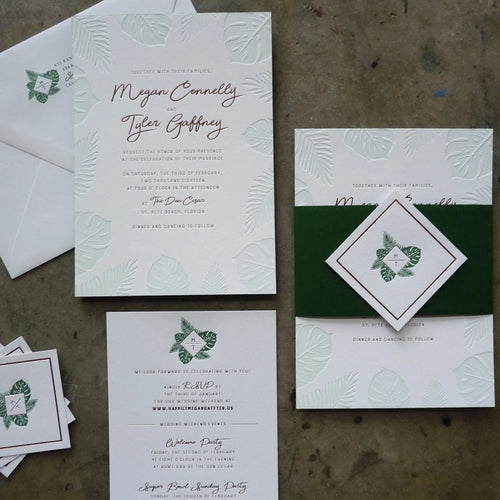Letterpress wedding invitation with Palm and Monstera leaves, gold foil, and elegant belly band