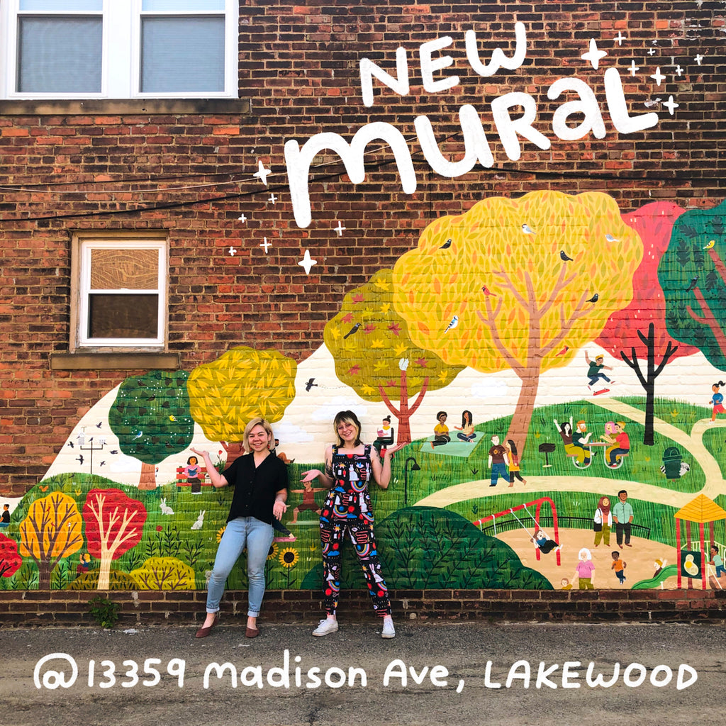 Two people standing infront of a mural with trees, people, and animals in a park