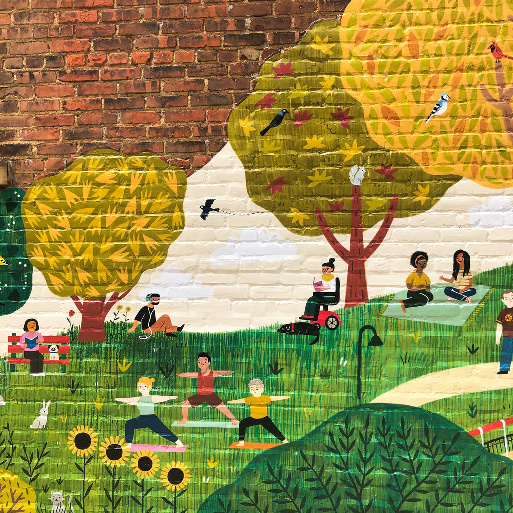 Section of mural with two people sitting on blanket and talking, a person in a motorized wheelchair reading, a person wearing headphones, a person sitting on a bench reading with a dog, a bird flying, three people doing yoga, sunflowers, and a cat hidden behind more leaves
