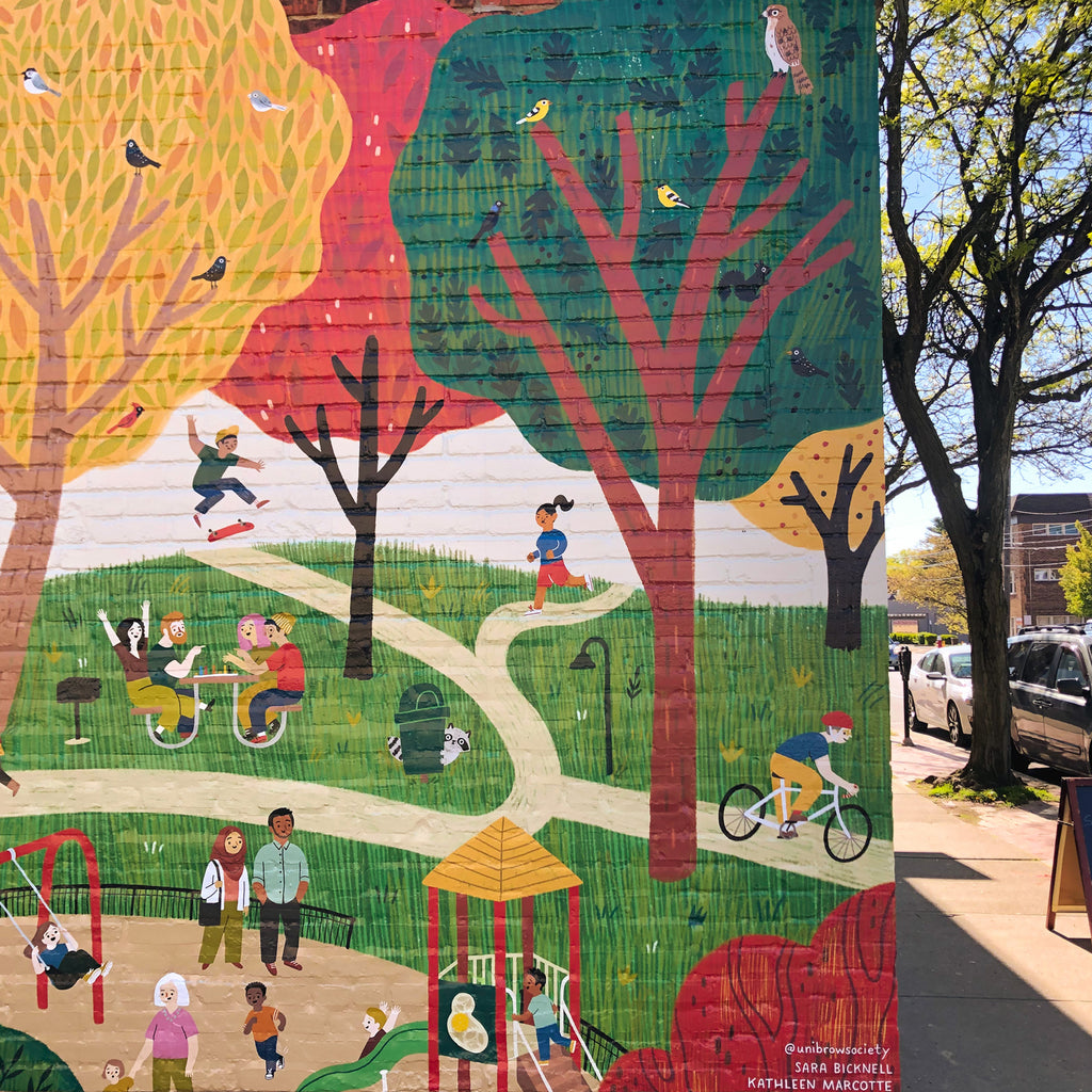 Section of mural with trees, children on a playground, a biker, a runner, a skateboarder, and a group of friends at a picnic table playing a board game