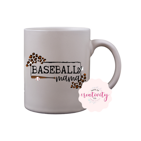 "White coffee mug with ""Baseball Mama"" graphic on the front, Taste Of Creativity CO. logo in the bottom right corner"