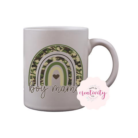 "White coffee mug with ""Boy Mama"" camouflage rainbow graphic on the front, Taste Of Creativity CO. logo in the bottom right corner"
