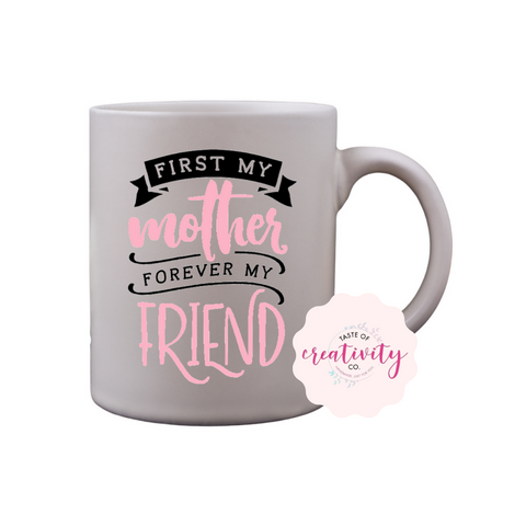 "White coffee mug with ""First My Mother, Forever My Friend"" graphic on the front, Taste Of Creativity CO. logo in the bottom right corner"