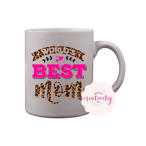 "White coffee mug with ""World's Best Mom"" graphic on the front, Taste Of Creativity CO. logo in the bottom right corner"