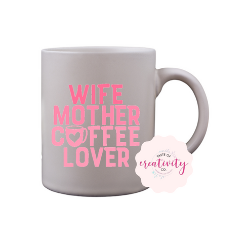 "White coffee mug with ""Wife, Mother, Coffee Lover"" graphic on the front, Taste Of Creativity CO. logo in the bottom right corner"