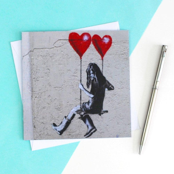 "Street Art Greetings Card ""Girl on a Swing with Balloons"" by JPS."