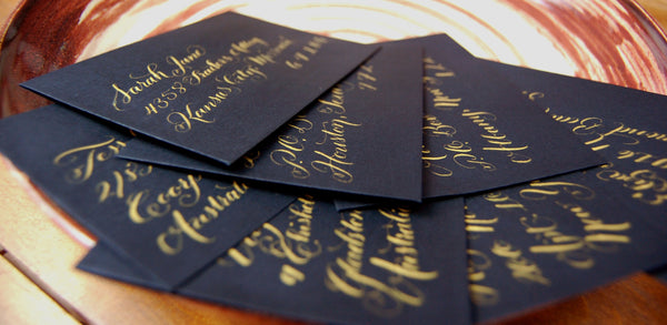 Pointed Pen Calligraphy on Black Linen envelopes with gold ink