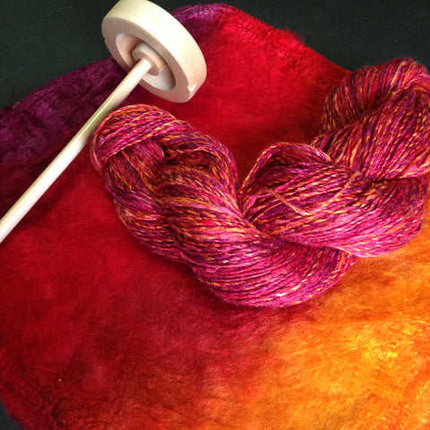 a skein of handspun silk yarn and a wooden drop spindle lay on a silk hankie dyed in strips of purple, red, and orange, matching the yarn