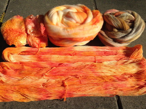 the dried yarns and rovings, in shades of orange and yellow, are laid out on concrete pavers in the sun