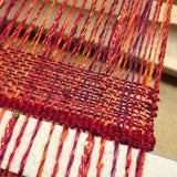 the very beginning of the weaving, showing the edge of a cardboard spacer and a couple inches of weaving