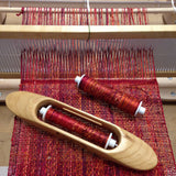 the woven scarf in progress on a small loom, with a boat shuttle and extra bobbin resting on the warp