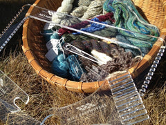 the clear acrylic frame loom and tools lean against a small basket of handspun yarn samples