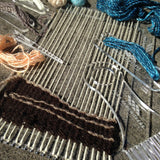 beginning of the weaving, with dark brown yarn and light brown highlights for the shore. other tools and yarns are scattered around the loom