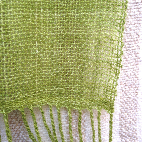 close up of a corner of the green scarf, loosely woven, with twisted fringe on the lower edge