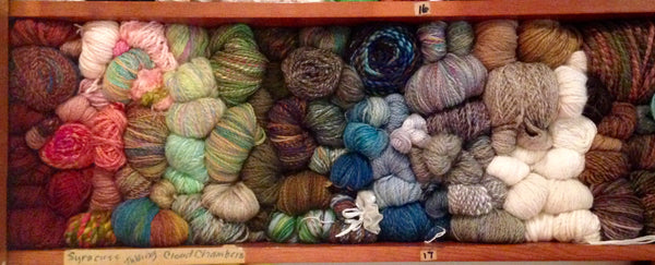 a shelf stuffed full of handspun yarns, somewhat arranged by color