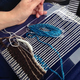 the loom with a bit of the water started, is resting on my lap in the car, with my hand visible at the left, holding the comb