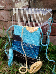 the loom leans against a pile of bricks on green grass, with half of the sky and moon now complete