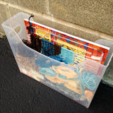 the clear plastic file box sits on pavement against a brick wall. the yarns and book are visible through the clear box