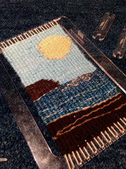 the completed weaving, still on the loom, lays at an angle on dark blue carpet