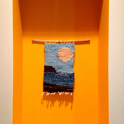 the completed weaving is mounted on a thin bamboo stick, and hangs in a wall niche painted golden yellow