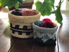 two soft baskets filled with yarn and pom poms, sitting on a counter with some plants behind