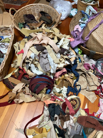 basket of fabric strips in variety of colors, mostly overflowing onto the floor
