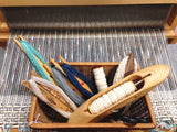 small basket of weaving shuttles holding a variety of yarns, resting on a stretched warp on a loom