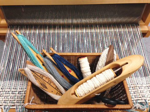 basket of shuttles wound with various yarns for the weft