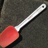 A red spatula with Dyes No Food written on the handle