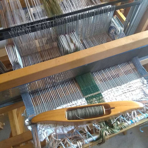floor loom set up with standard warp, plus weaving cards inserted behind the reed for decorative selvedges and decorative band running down the center