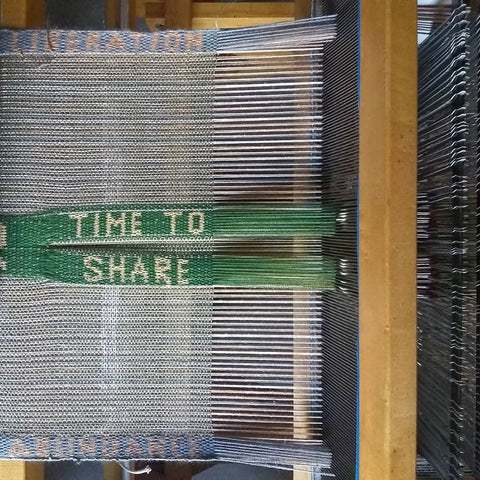 "overhead view of weaving in progress, showing card-woven band in the center of plain warp, reading ""time to share"""